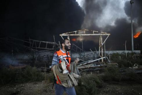 Palestinian firefighter reacts as he tries to put out a fire at Gaza's main power plant in the central Gaza Strip