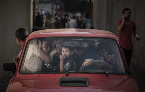 Palestinian families leave their apartments in El-Joundi tower to a safer location after Israeli strike in Gaza City,