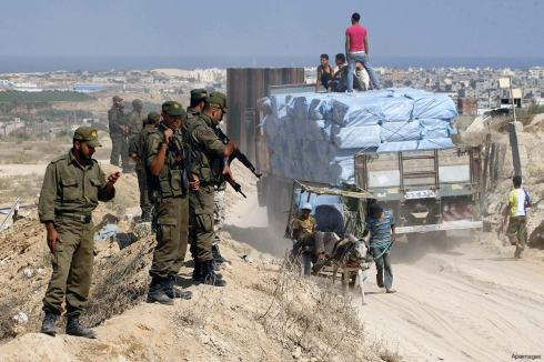 palestinian-border-police-monitor-a-truck-in-the-Gaza-Strip-containing-construction-materials