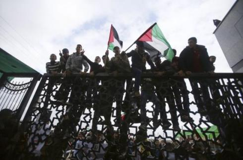 Palestinians climb a gate during a rally calling on Egyptian authorities to open the Rafah border crossing, at the crossing in the southern Gaza Strip