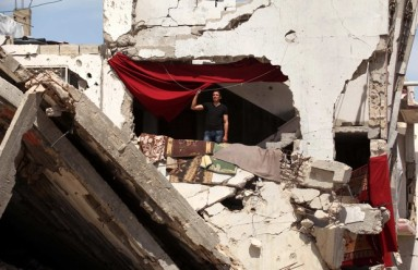 A Palestinian man stands on the rubble of his house that was destroyed during the 50-day Israeli war on Gaza Strip in the summer of 2014
