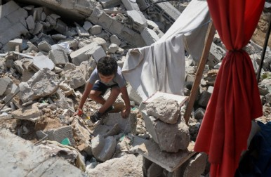 A Palestinian boy collects his belongings from under the rubble of his house which witnesses said was destroyed during the Israeli offensive in Shejaiya neighborhood