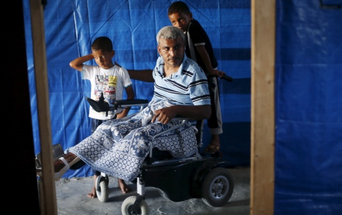 Sons of Palestinian maths teacher Ali Wahdan stand around him inside their makeshift shelter, in Beit Hanoun town, in the northern Gaza Strip July 6, 2015. Wahdan, a maths teacher from Gaza, lost his wife, 11 members of his family and a leg to Israeli bombardment of the town of Beit Hanoun, in the north of the Gaza Strip, during last year's war between Israel and Hamas. Nearly 12 months on, doctors have decided to amputate his other leg. It is a cruel reminder of how little progress he has made since the 50-day war. In almost all respects, his life and prospects have crumbled. Picture taken July 6, 2015.   REUTERS/Suhaib Salem  - RTX1JIZ5