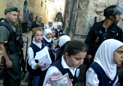 "Palestinian school children walk past Israeli riot policemen during clashes near the Al-Aqsa mosque compound in Jerusalem's old city on October 25, 2009. Jordan demanded Israeli police stop entering Al-Aqsa, Islam's third holiest shrine, warning that ""dangerous provocations"" by the Jewish state threaten peace efforts in the Middle East. Police twice entered Al-Aqsa compound on Sunday after Palestinian demonstrators threw stones at visitors to the holy site, known to Muslims as Al-Haram Al-Sharif (the Noble Sanctuary) and to Jews as the Temple Mount . Photo by Mahfuz Abu Turk"