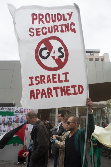 <p> An activist carries posters calling for support of the Boycott Divest Sanction (BDS) campaign and the boycottt of British private security company G4S during a protest marking International Palestinian Prisoners' Day, Brussels, Belgium, April 17, 2014. G4S plays a key role in Israel's occupation system, providing security services and equipment to Israeli prisons, checkpoints, the Separation Wall and the Israeli military and police. </p>