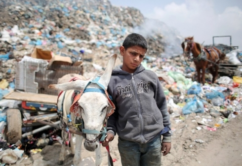 Palestinian Hussein Al-Najjar, 14-years-old, stands with a donkey-pulled cart loaded with recyclable waste and other items he collected in hope to be able to sell them, at a garbage dump in Rafah, in the southern Gaza Strip on April 16, 2015. AFP PHOTO / SAID KHATIB  / AFP PHOTO / SAID KHATIB